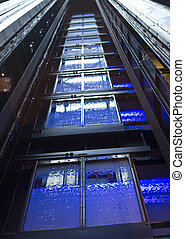 Elevator Shaft - A blue glass elevator shaft in a lobby
