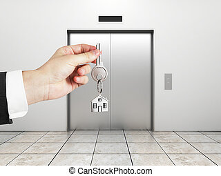 hand holding key - elevator with closed doors and hand ...
