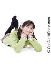 Eleven year old girl lying on floor relaxing - Biracial ...