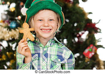 Elf boy holding gingerbread man