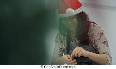 Elf is repairing wonderful toy to hang it on Christmas tree.