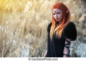 Elf women with fiery hair on nature. Beautiful young fantasy...