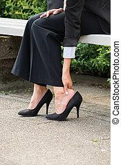 ella/los/las de mujer de negocios, mano, el quitar, zapatos de taco alto