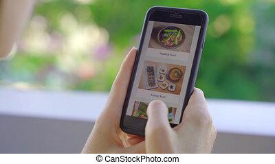 elle, balcon, jeune, appartement, smartphone., elle, nourriture, utilisation, séance femme, déjeuner, ordres, ligne