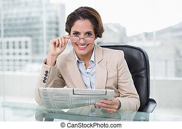 elle, femme affaires, tenue, bureau, journal, sourire