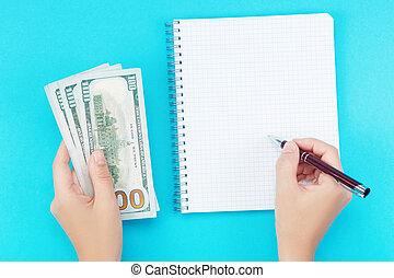 elle, femme, argent, cahier, arrière-plan bleu, écriture main, tient