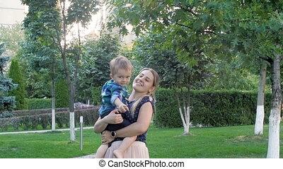 elle, mère, parc, fils, embrasser, baisers, sourire, enfantqui commence à marcher, heureux