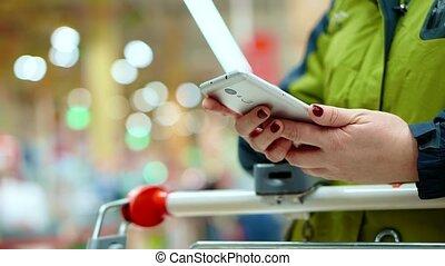 elle, marchandises, supermarché, attente, main, products., penchant, elle, tient, smartphone, femme, panier, file, contrôle