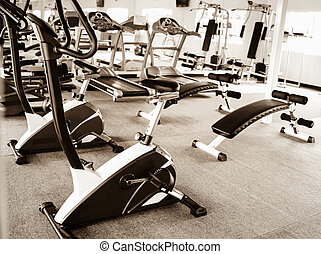 elliptical cross trainer in a row in a gym with earth tone...