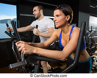 elliptical walker trainer man and woman at black gym...