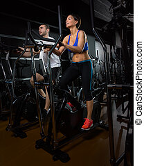 elliptical walker trainer man and woman at black gym
