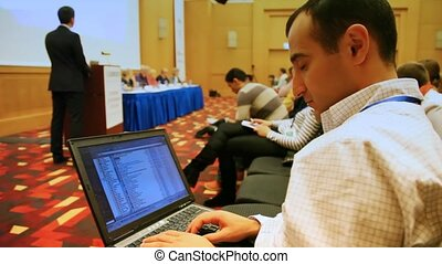 Elnur Amikishiyev looks at conferences in laptop close up