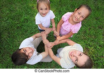 eltern, mit, kinder, stehen, haben, angeschlossene hände, crosswise, draufsicht