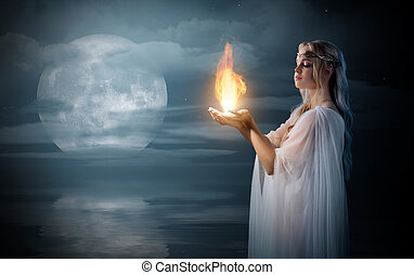 Elven girl holding fire in palms at sea shore