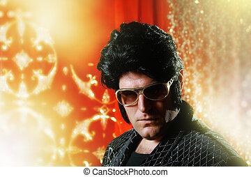 Elvis Presley impersonator over glowing background.
