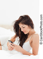 elzáródik, nő, használ, neki, smartphone, mint, ő, fekszik,...