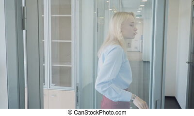Emaciated female employee leaves office, sighs, takes hold of head.