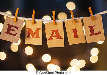 The word EMAIL printed on clothespin clipped cards in front of defocused glowing lights.