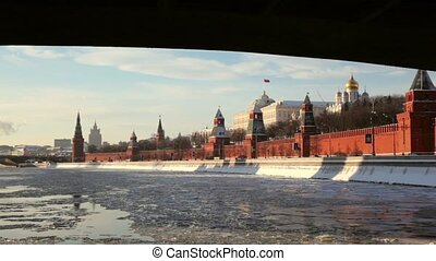 Embankment and red brick walls of Moscow Kremlin and Ivan Great Bell Tower at winter, view from river when ship comes up from under the bridge