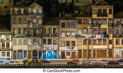traditional quaint houses in the old, vintage and touristic ribeira district of Porto at night timelapse, Portugal