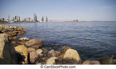 Embankment of Baku, Azerbaijan. The Caspian Sea, Stones and Skyscrapers. Slow Motion
