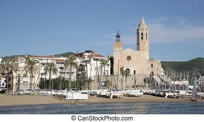 Embankment of Spanish city of Sitges with views of beach and Church of St. Bartholomew and Santa Tecla on sunny autumn day, Catalonia. High quality FullHD footage