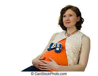 embarazada, adulto, mujer, juego, con, bebé zapatos, se sentar sobre una silla