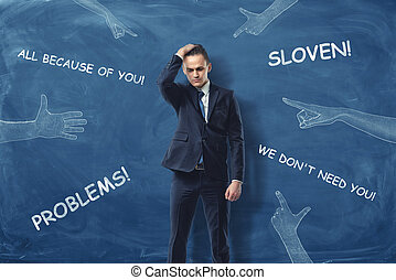 Embarrassed businessman standing near dark blue wall with hands pointing to him and blaming words drawn on it.