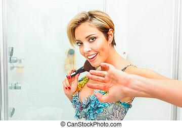 Embarrassed pretty woman in bathroom using fluffy brush