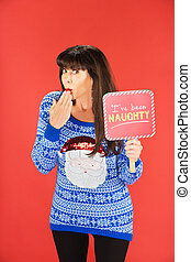 Embarrassed woman in blue sweater holding naughty sign