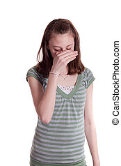 Embarrassment - a young teenage girl with her hand covering...