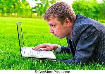 ember, dolgozó, noha, egy, laptop, fekvő, képben látható, a, pázsit