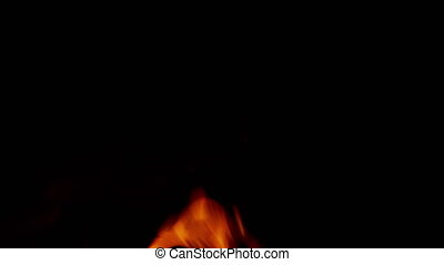 Embers rising fromfire on dark background. Flaming bonfire in night forest. Slow motion.