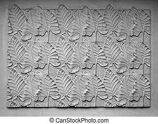 Decorative embossed and textured leaves of plants on wall