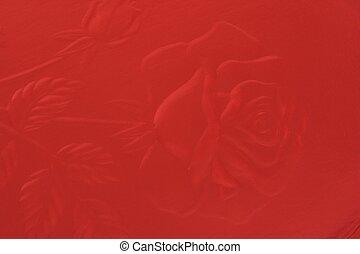 Macro of a rose embossed on red cardboard.