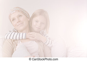 Embrace of cancer woman and daughter