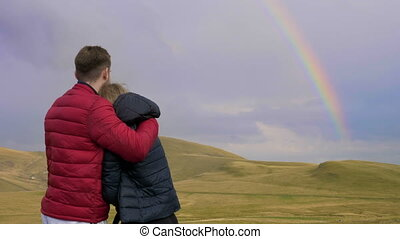 Embraced boy and girl couple of lovers admiring the...