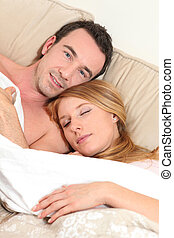 Embraced couple in bed