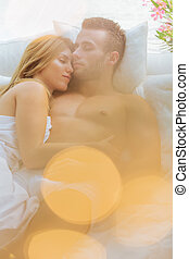 Embraced couple sleeping in bed