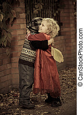 Cute children hugging each other at a park. Retro style.