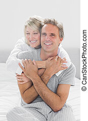 Embracing couple smiling at camera at home in bedroom