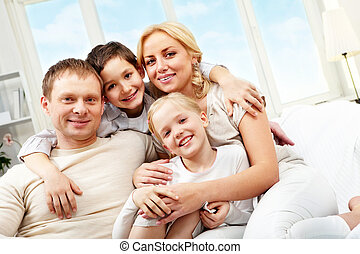 Embracing family - A family of four sitting on sofa,...