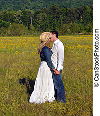 Embracing in field of yellow flowers - Young couple embrace...