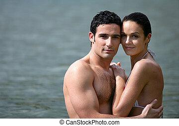 embracing pares, enquanto, banhar-se, em, a, mar