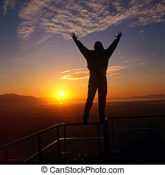 sunset or sunrise as a embraces the sun while standing on a high railing