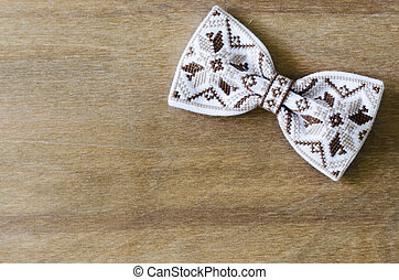 Embroidered Bow Tie on Wooden Brown Background.