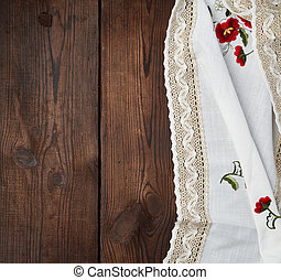embroidered white dishcloth with lace on a brown wooden background