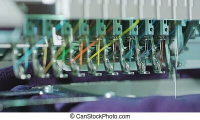 Embroidery machine starting to embroider with a needle on the fabric