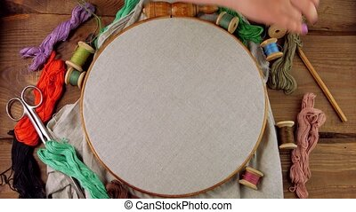 Embroidery needlework background Linen in hoop mockup. Colorful floss thread scissors card tag in child hands. Handmade ethnic clothes towel tablecloth.New normal lockdown hobby crafts stitch tutorial