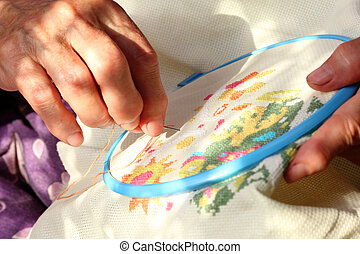 embroidery - Hands of an old woman busy embroidering